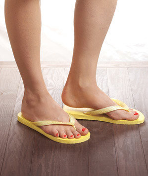womans-feet-yellow-flip-flops