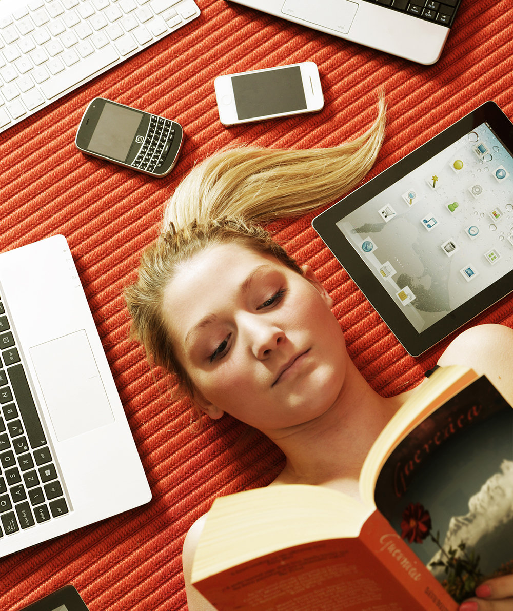 woman-reading-book-surrounded-by-tech